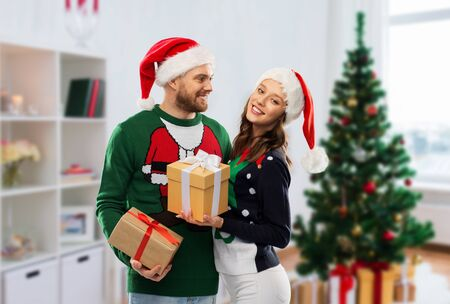 people and winter holidays concept - happy couple in santa hats with gifts in ugly sweaters over christmas tree at home background Stockfoto