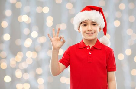 christmas, holidays and childhood concept - smiling little boy in red polo t-shirt and santa helper hat showing ok hand sign over festive lights background Stock fotó