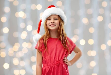 christmas, childhood and holidays concept - smiling red haired girl posing in santa helper hat over festive lights background
