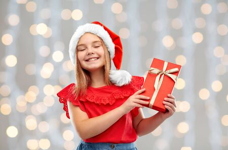 Concepto de Navidad, infancia y vacaciones - sonriente niña complacida posando con sombrero de ayudante de santa con caja de regalo sobre fondo de luces festivas