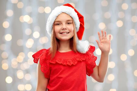 christmas, childhood and holidays concept - smiling girl posing in santa helper hat waving hand over festive lights background