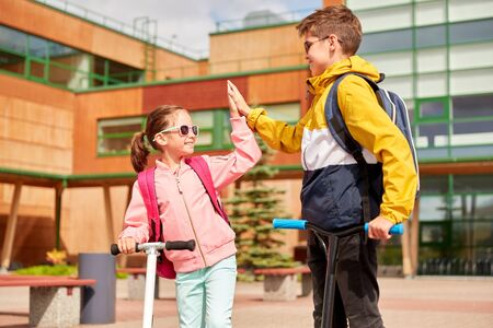 education, childhood and people concept - happy school children with backpacks and scooters making high five outdoors