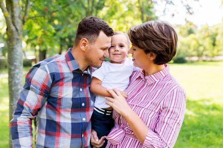 concepto de familia, ocio y personas - feliz madre, padre e hijo pequeño en el parque de verano Foto de archivo