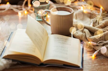 book and cup of coffee or hot chocolate on table