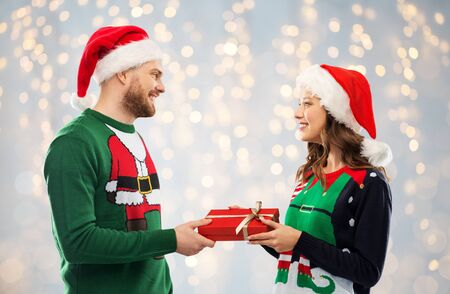 happy couple in sweaters with christmas gift Stock fotó
