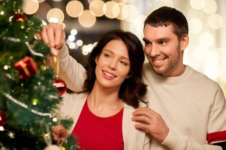 happy couple decorating christmas tree at home