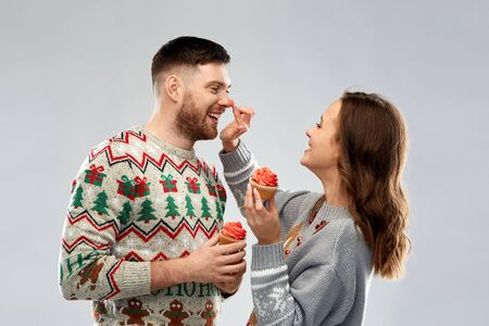 couple with cupcakes in ugly christmas sweaters Stockfoto - 130625237
