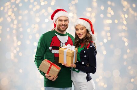happy couple in sweaters with christmas gifts