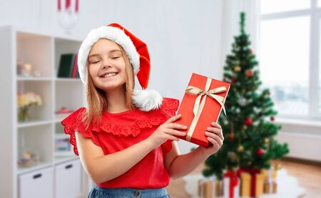 girl in santa hat with christmas gift at home 写真素材