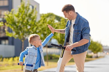 family, leisure and fatherhood concept - happy father and little son with scooters making high five in city Imagens