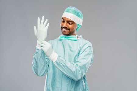 indian male doctor or surgeon putting glove on