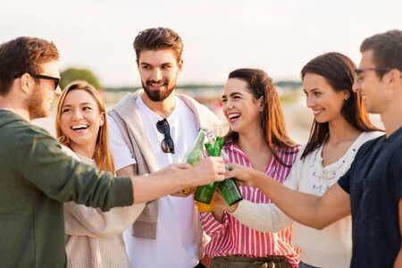 friendship and leisure concept - group of happy friends toasting non alcoholic drinks on summer beach