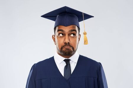 confused indian graduate student in mortar board Foto de archivo