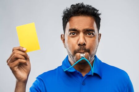 Árbitro indio silbando y mostrando tarjeta amarilla
