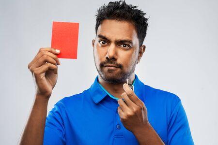 Árbitro indio con silbato mostrando tarjeta roja