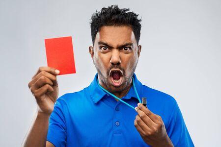 Árbitro indio enojado con silbato mostrando tarjeta roja Foto de archivo