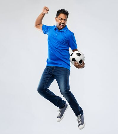 man or football fan with soccer ball jumping