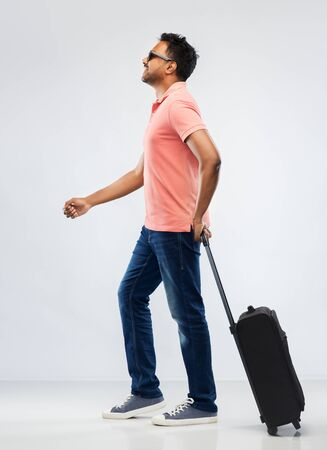 smiling indian man in polo shirt with travel bag