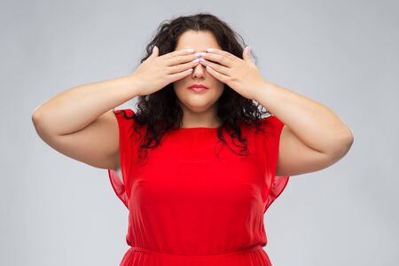 woman in red dress closing her eyes by hands