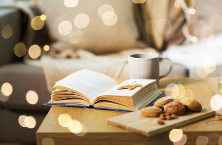 book with autumn leaf, cookies and tea on table