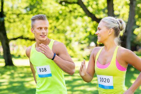 glückliches Paar Sportler, die mit Abzeichennummern laufen Standard-Bild