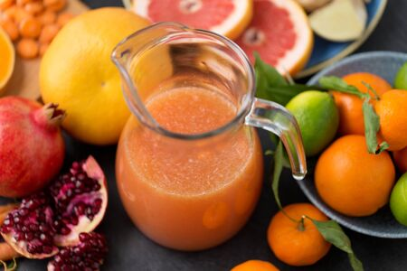 glass jug of juice with fruits and vegetables