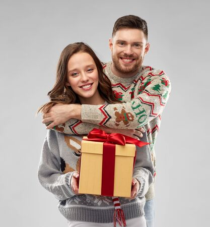 happy couple in christmas sweaters with gift box Stockfoto - 130587464