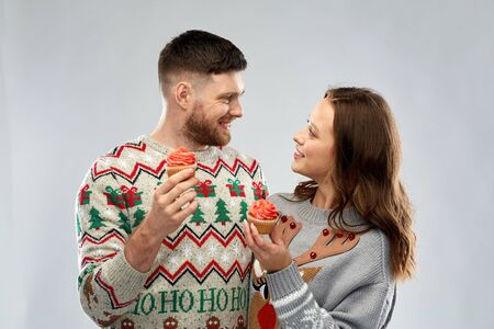 couple with cupcakes in ugly christmas sweaters