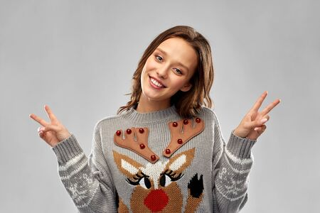 woman in ugly christmas sweater showing peace sign