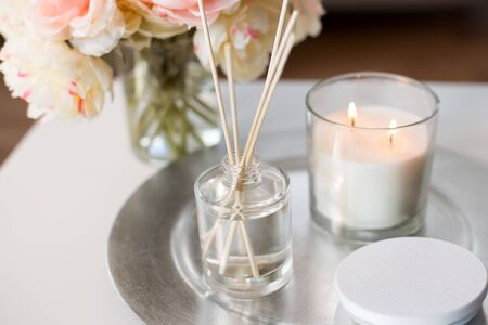 aroma reed diffuser, candle and flowers on table