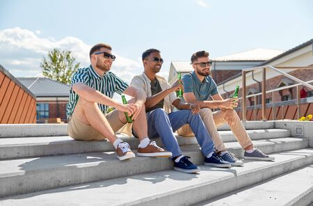 happy male friends drinking beer on street