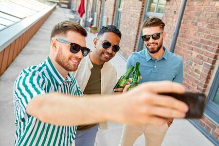 men drinking beer and taking selfie by smartphone