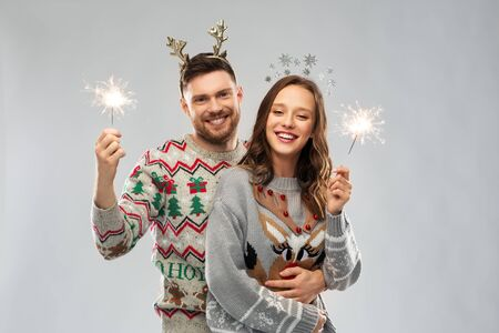 happy couple in christmas sweaters with sparklers