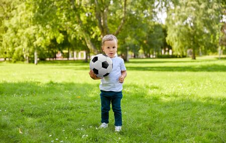 little baby boy with soccer ball at summer park