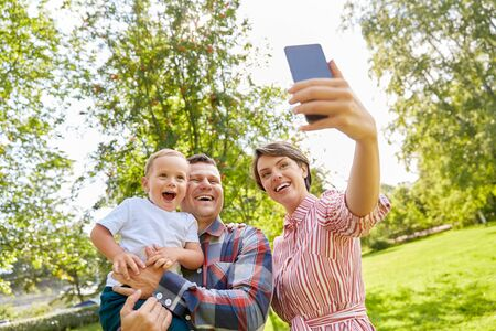 happy family taking selfie at summer park Stock Photo