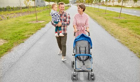 family with baby and stroller walking along city