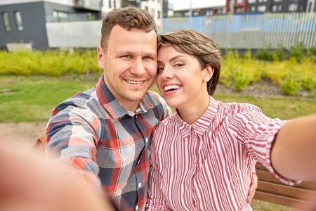 happy couple in park taking selfie outdoors