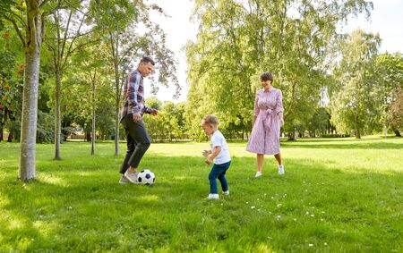 happy family playing soccer at summer park Archivio Fotografico