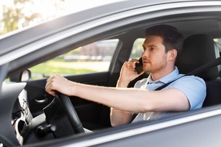 man driving car and calling on smartphone