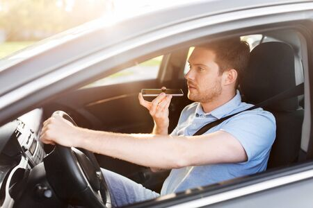 man driving car and recording voice by smartphone Stock Photo