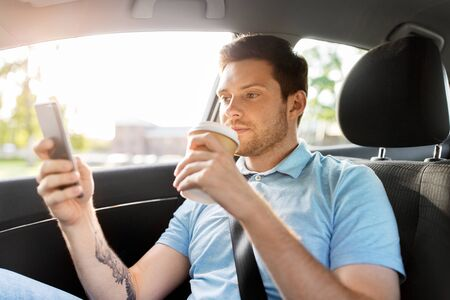 passenger drinking coffee using smartphone in car
