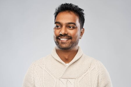 indian man in knitted sweater over gray background