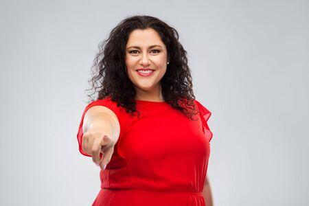 glückliche Frau im roten Kleid, die mit dem Finger auf dich zeigt