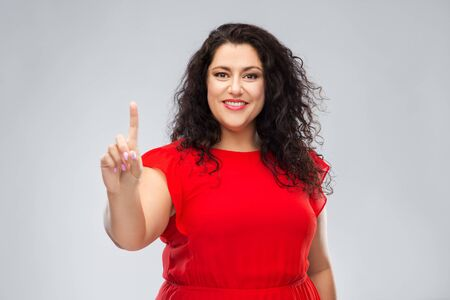 happy woman in red dress showing one finger 写真素材
