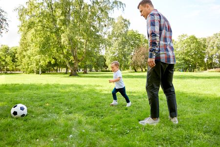 father with little son playing soccer at park Stock Photo