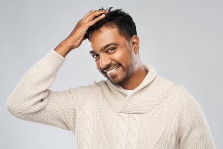 indian man in knitted sweater touching his hair Stockfoto