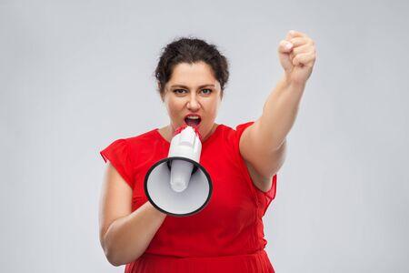 mujer en vestido rojo hablando por megáfono