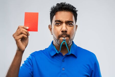 indian referee whistling and showing red card Фото со стока