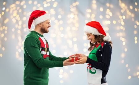 happy couple in ugly sweaters with christmas gift