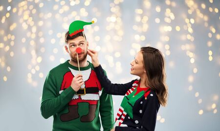 couple with christmas party props in ugly sweaters Stockfoto - 130745178